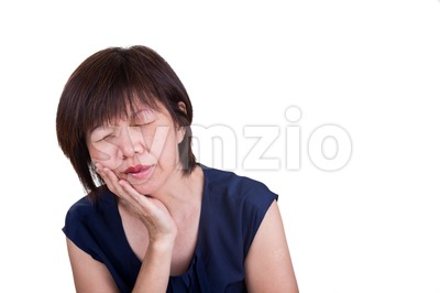 Asian woman suffering intense toothache pain with hands over face Stock Photo