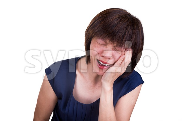 Asian woman in intense pain with hands over face Stock Photo