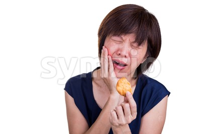 Asian women with intense toothache pain after biting cookie Stock Photo