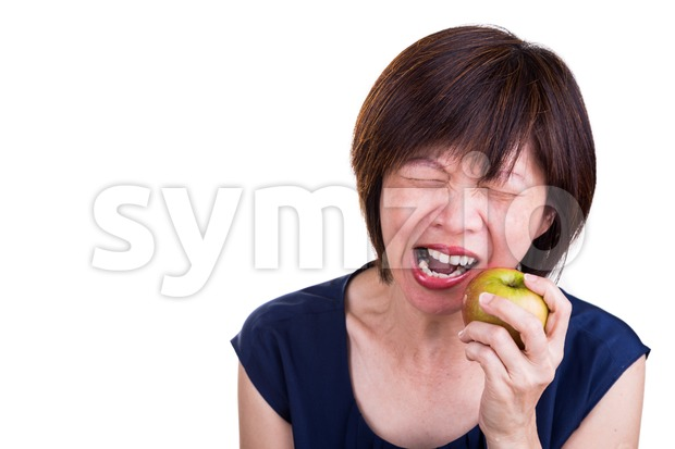 Asian women with intense toothache pain after biting apple Stock Photo