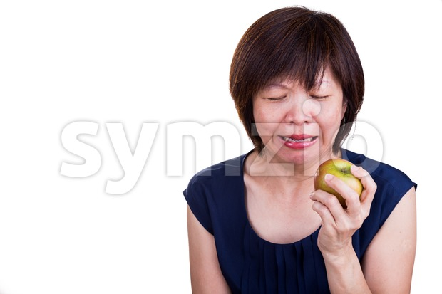 Asian women with intense toothache pain after biting apple, on white background