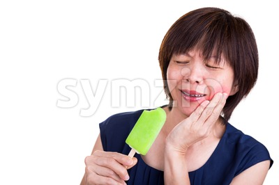 Asian women suffering intense toothache pain after biting ice cream Stock Photo