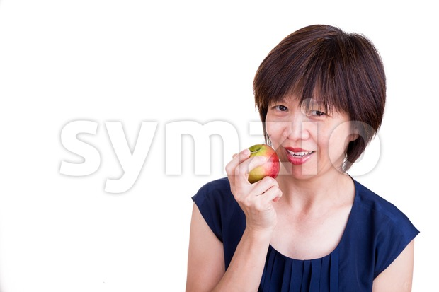 Pretty Asian women holding apple promotes healthy diet Stock Photo