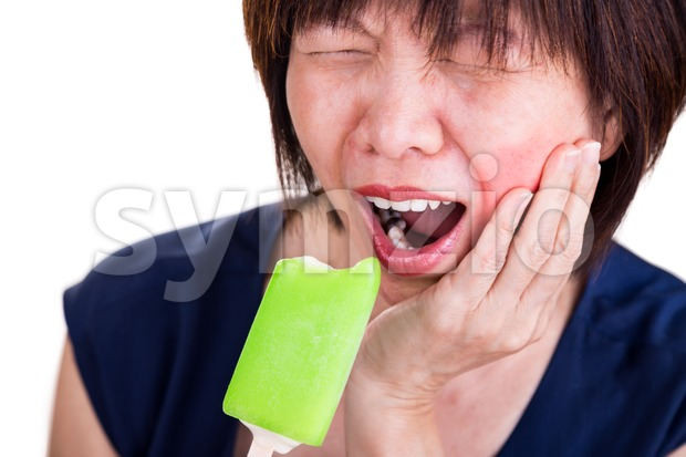 Closeup of Asian women with intense toothache pain after biting ice cream, on white background