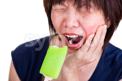 Closeup Asian women with toothache pain after biting ice cream Stock Photo