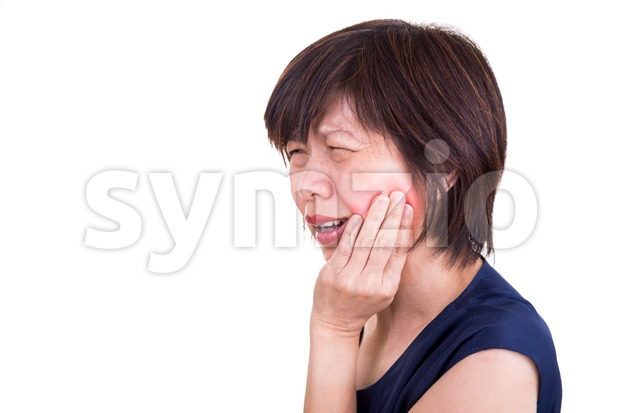 Asian woman in intense toothache pain with hands over face with white background