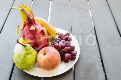 Fresh mixed fruits on plate served on wooden table Stock Photo