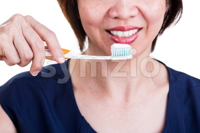 Asian women with beautiful teeth holding toothbrush and toothpaste Stock Photo