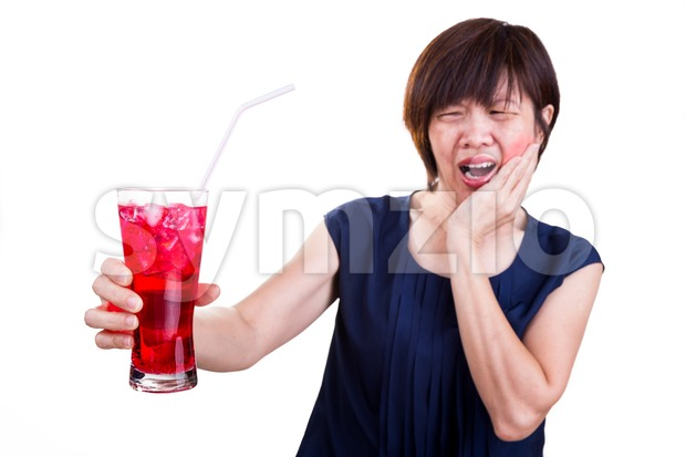 Focus on ice cold drink with women suffering intense toothache pain as background