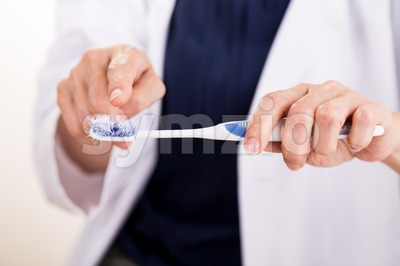 Dentist pointing at old worn out toothbrush bristle Stock Photo