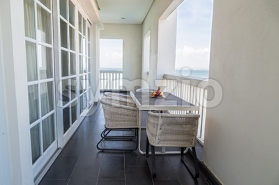 Relaxing balcony with table, chairs, fruits and with sea view Stock Photo