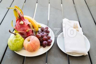 Mixed fruits on plate served on table with napkin fork Stock Photo