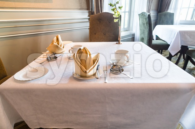 Perspective view of elegant cozy dining table with cutleries set for two person