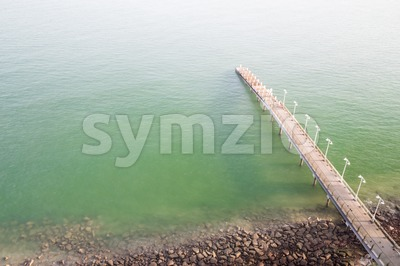 Jetty on the coast reaches out to calm green sea Stock Photo