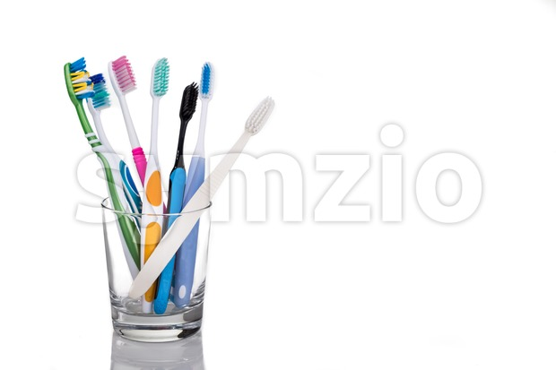 Toothbrushes with different head and bristle design placed in glass on white background