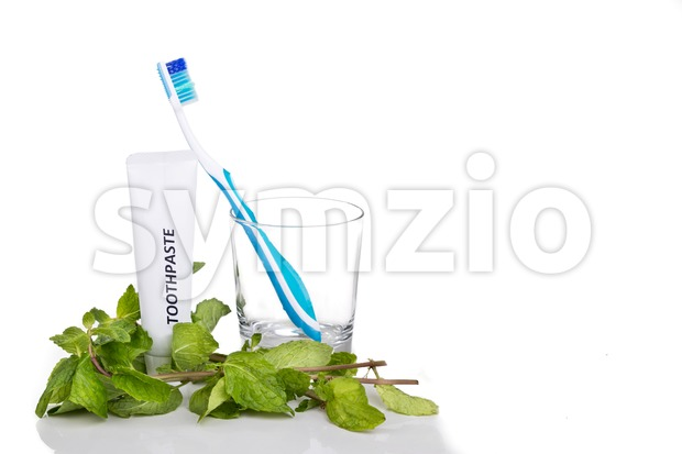 Soft tapered bristle toothbrush with toothpaste and mint leafs on white background