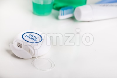 Dental floss focused with  toothbrush, toothpaste, mouthwash, at background Stock Photo