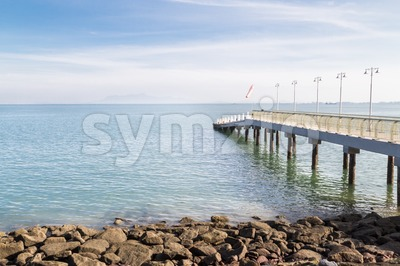 Jetty on the coast reaches out to calm blue sea Stock Photo