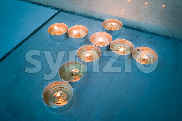 Glowing candle tea lights in Christian crucifix cross formation