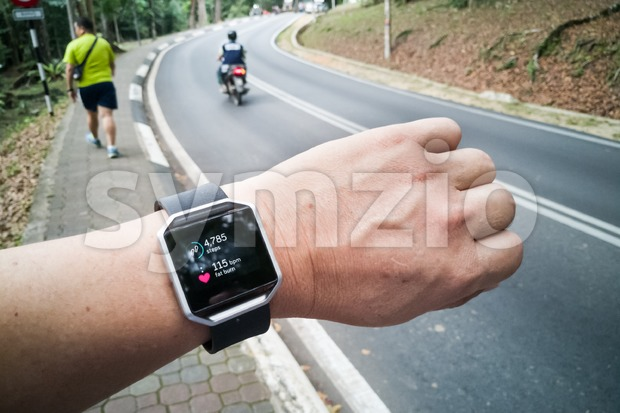 Perspective view of person checking tracker watch for steps and heartbeat rate during exercise workout