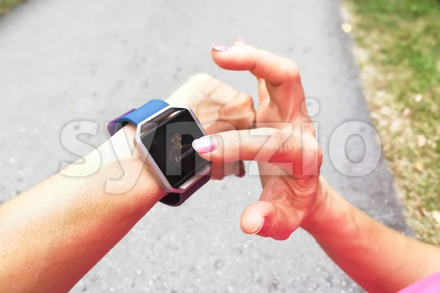 Perspective view of person checking tracker watch during exercise Stock Photo