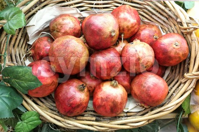Red Pomegranate whole fruit displayed on basket Stock Photo