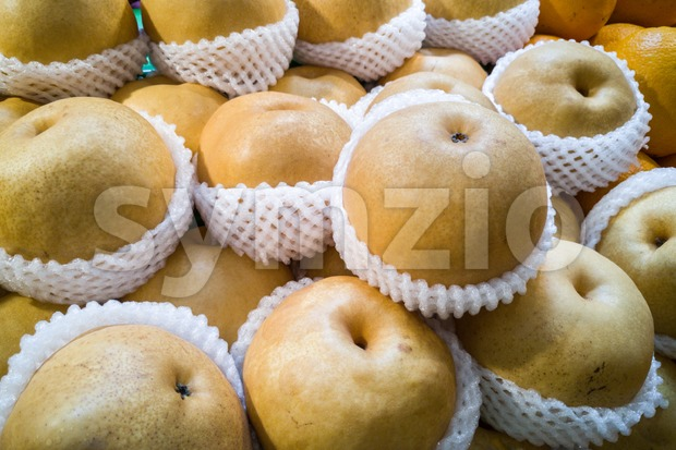 Whole yellow nashi pear wrapped in protective foam Stock Photo