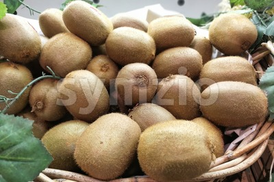 Whole natural organic Kiwi fruit in basket Stock Photo
