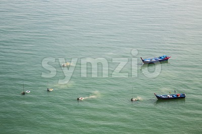 Fishermen harvesting shellfish and fish from the sea with net Stock Photo