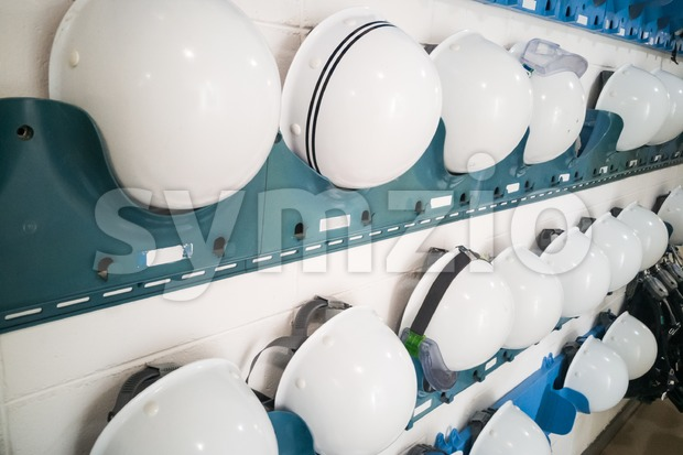 Industrial protection white safety helmet and goggles on storage shelf in factory