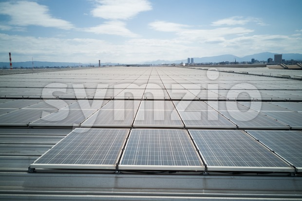 Solar panels on roof of industial building generate renewable electricity