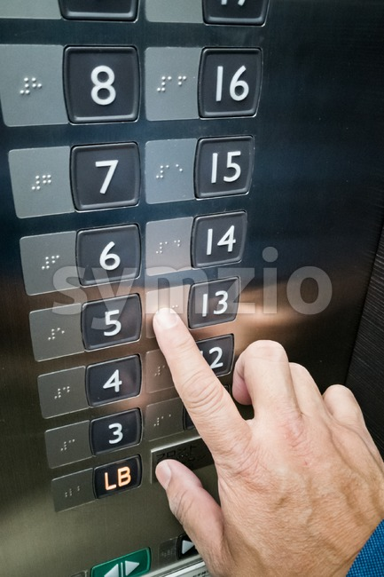 User finger reading Braille on elevator panel Stock Photo