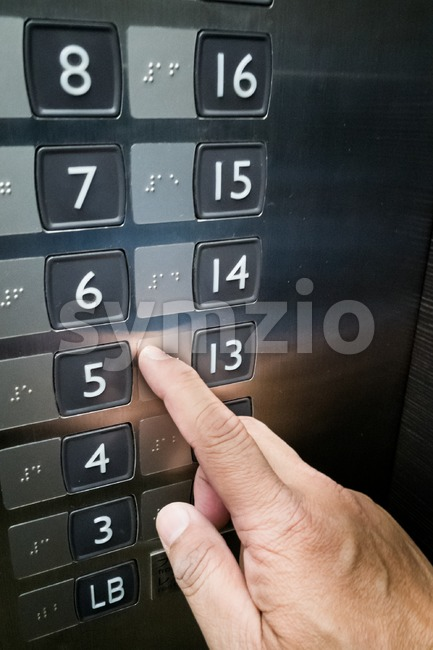 Closeup on user with vision disability reading Brialle on elevator panel with finger