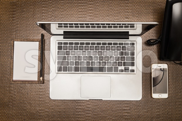 Essential gadgets of mobile phone, laptop and note pad for mobile office setup.