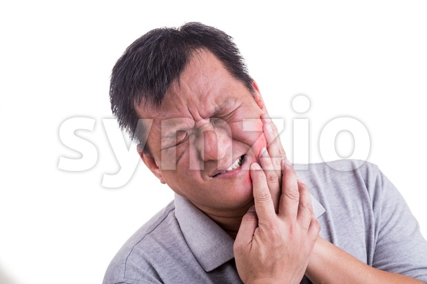 Matured man suffering intense toothache pain with hands over face Stock Photo