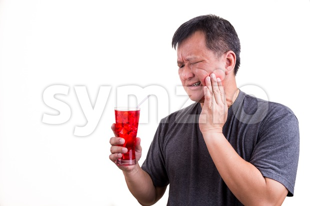Focus on ice cold drink with matured man suffering intense toothache pain as background