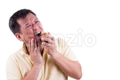 Conceptual man with toothache pain after biting apple with thorns Stock Photo