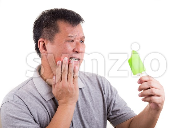 Matured man suffering intense toothache pain after biting ice cream, on white background