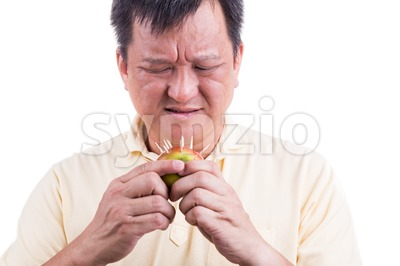 Conceptual of man hesitate to bite apple with thorns Stock Photo