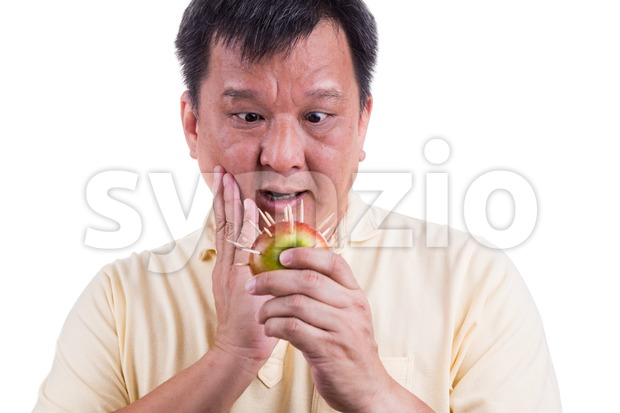 Conceptual of man holding apple with thorns fear suffer toothache Stock Photo