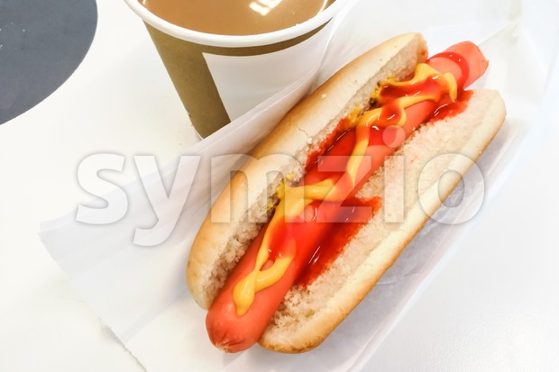 Simple hot dog sandwich breakfast with mustard ketchup and coffee