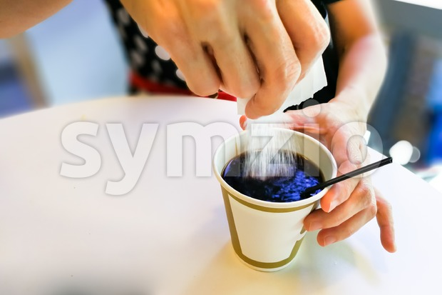 Women pouring lots of sugar granules from sachet into black coffee, and is unhealthy