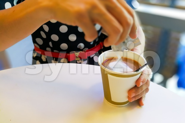 Hand pouring unhealthy non dairy creamer from sachet into coffee Stock Photo