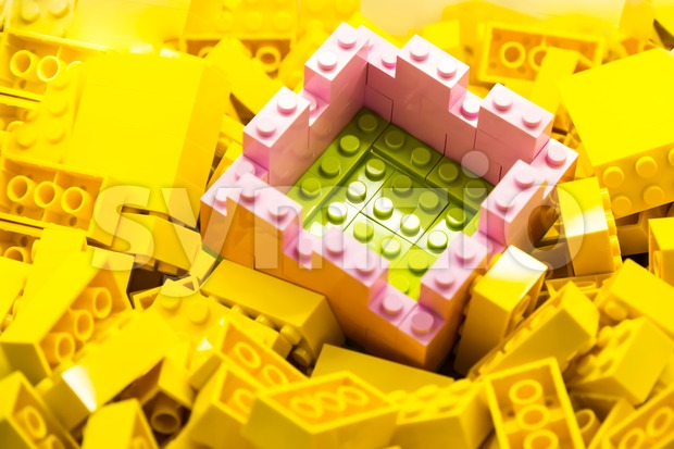 Concept of selective focus on secured and protected green area within wall constructed using building blocks, against heaps of yellow bricks Stock Photo