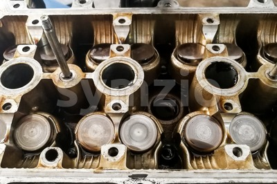 Worn uto car engine valves being serviced at garage Stock Photo