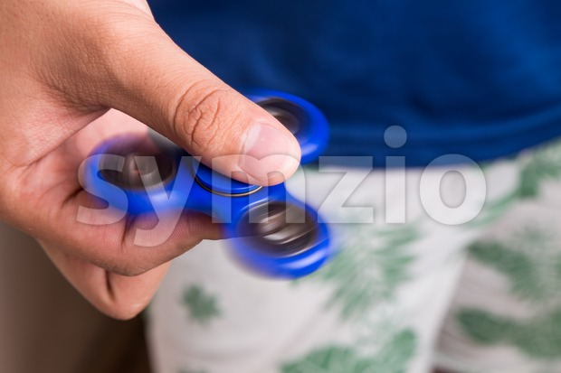 Teenager holding a spinning fidget spinner Stock Photo