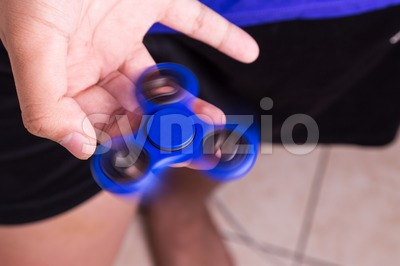 Teenager spinning a fidget spinner on finger Stock Photo