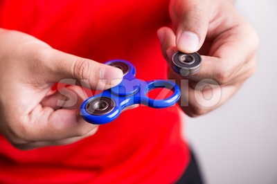 Person holding dislodged weight from fidget spinner, dangerous for kids Stock Photo