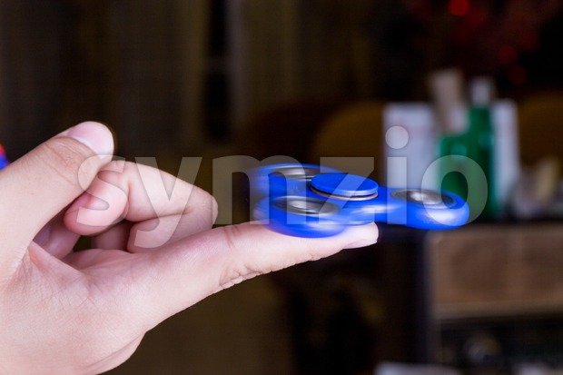 Close-up of teenager spinning a fidget spinner on finger Stock Photo