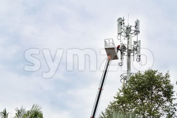 Two workers on crane and protective harness installing mobile network communication antenna